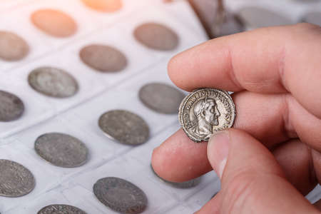 Numismatics. Old collectible coins made of silver on a wooden table. A collector holds an old coin. Ancient coin of the Roman Empire.