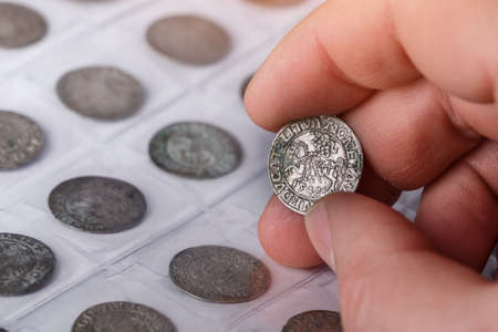 Numismatics. Old collectible coins made of silver on a wooden table. A collector holds an old coin.