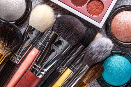 Professional makeup brushes and tools, makeup product set.A set of decorative cosmetics on a gray background. Flat lay, top view.