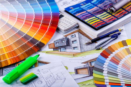 RUSHMOOR, UK - APRIL 30,2020: Interior designer's working table, an architectural plan of the house, a color palette. Drawings and plans for house decoration.Construction concept 에디토리얼