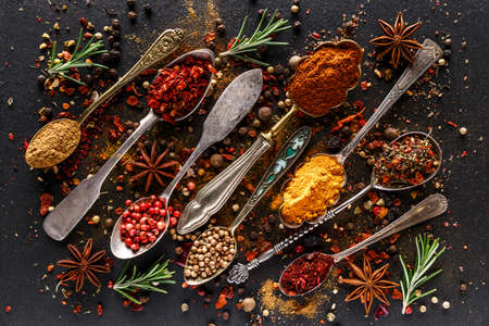 Various spices a vintage spoons on stone table. Colorful Herbal and Spices Oriental marketplace.Top view. Cafe concept. Delicious food delivery.