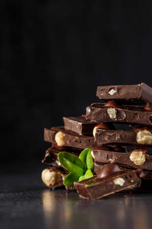 Stack of chocolate slices with mint leaf. Hazelnut and almond milk and dark chocolate pieces tower. Sweet food photo concept. The chunks of broken chocolate
