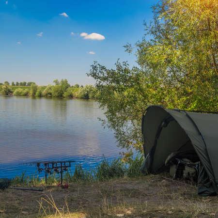 Fishing adventures, carp fishing. Angler, at sunset, is fishing with carpfishing technique. Camping on the shore of the lake.Carp Fishing Sunset