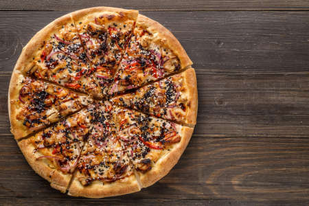 Fresh pizza with tomato sauce, black olives, mozzarella cheese, ham on wooden table closeup. Space for text or copy space. Pizza menu. Restaurant menu advertise
