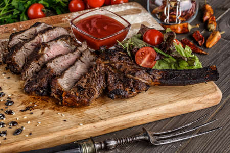 Grilled beef steak, herbs and spices on a dark table. Top view. Free space for your text. 스톡 콘텐츠