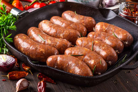 Grilled sausages, homemade, cast iron skillet or frying pan with tomatoes, garlic and rosemary. Brazilian barbecue. copy space
