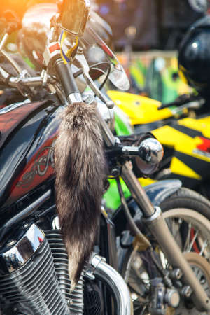 The chromed handlebar of a motorcycle.Travel and freedom, outdoor activities. View of motorcycle handlebar in the background many motorbikes blurred, concept of speed and travel in nature