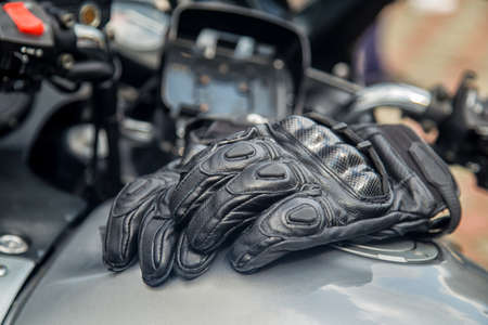 moto gloves. Motorcyclist arm protection. View of motorcycle accessories. Items included motorcycle helmet, keys and jacket. Motorcycle travel dream concept.