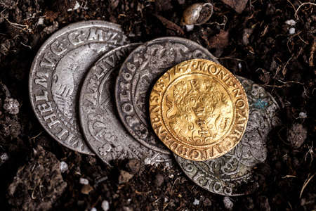 Closeup view of medieval European gold and silver coins.Old Polish coins.Zygmunt III Waza.Ancient gold and silver coins.Numismatics.silver coins covered in dirt.Antikvariat.
