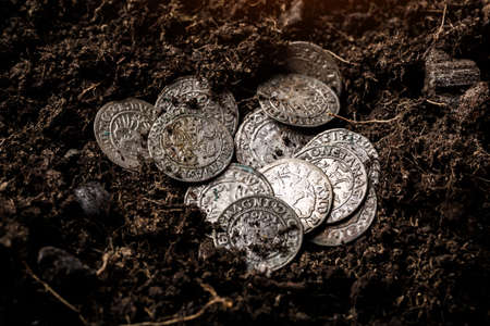 Closeup view of medieval European silver coins.Zygmunt III Waza.Ancient silver coins.Numismatics.silver coins covered in dirt.Antikvariat. 스톡 콘텐츠