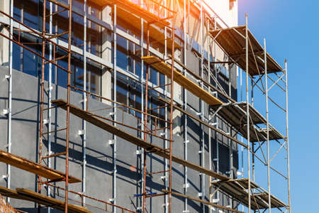 Extensive scaffolding providing platforms for work in progress on a new apartment block, Tall building under construction with scaffolds, Construction Site of New Building