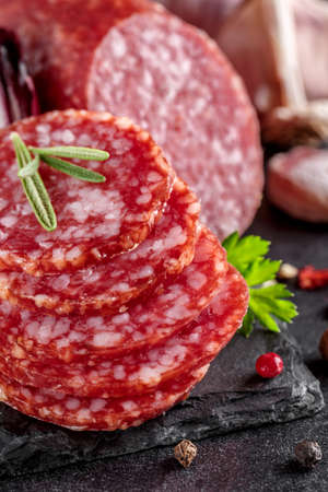 Traditional smoked salami sausage with spices. Salami sausage slices on a black chopping Board. Dark background.