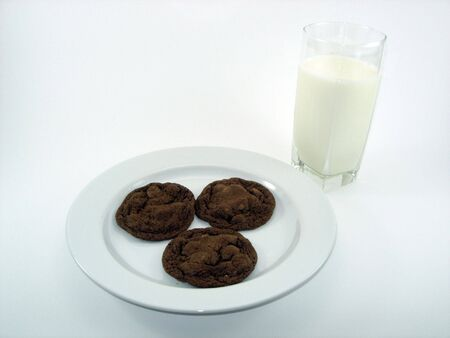 A plate of chocolate cookies and glass of milk