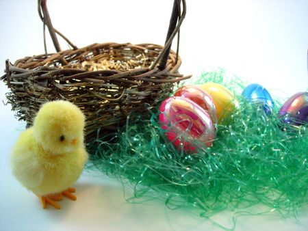 A collection of Easter eggs next to a basket and chick