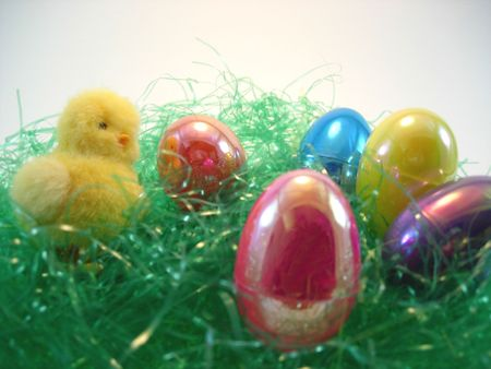 A collection of Easter eggs and a chick on grass Stock Photo
