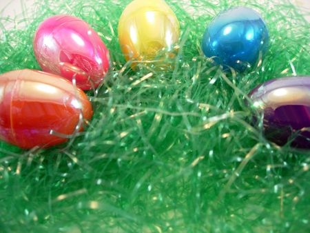 An assortment of bright Easter eggs on grass