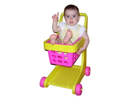 A  girl raising her hand in a toy shopping cart Stock Photo