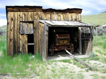 An old western carriage parked in an abandoned garage photo