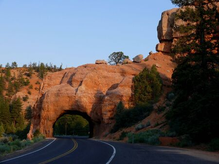 A road going through a tunnel carved out of rock photo