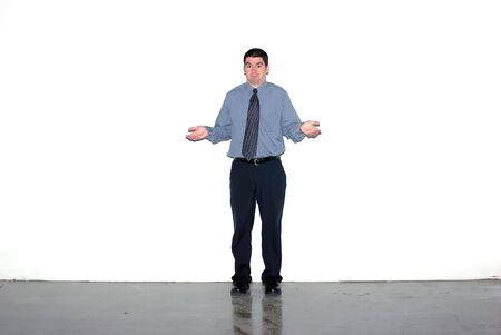 A man shrugging against a grungy white wall