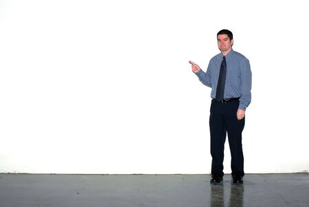 A man pointing to a grungy white wall