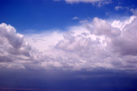 A bright blue sky above raining storm clouds Stock Photo