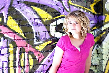 A beautiful young woman leaning against a wall covered in graffiti Stock Photo