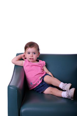 A little girl on a green leather chair in front of a white background Stock Photo