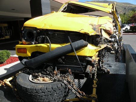 strapped: A wrecked yellow SUV strapped to a trailer Stock Photo