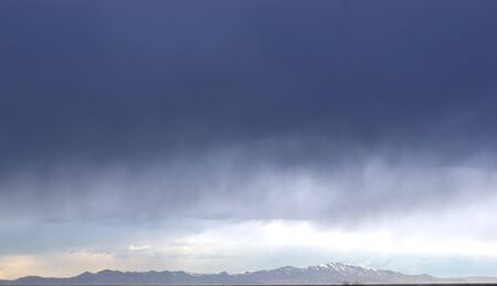 Storm clouds blowing in over a mountain range