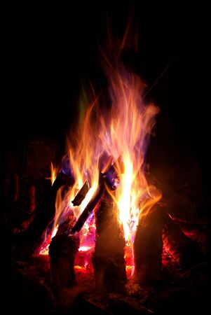 A large log camp fire with sparks Stock Photo