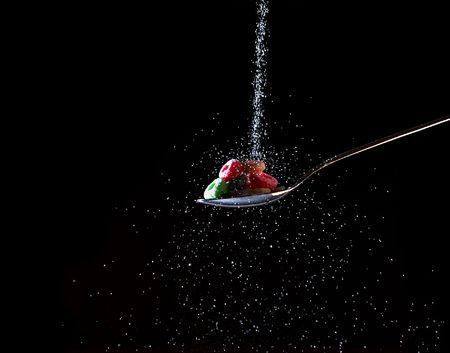 sweeten: Sugar poured on cereal in a spoon Stock Photo