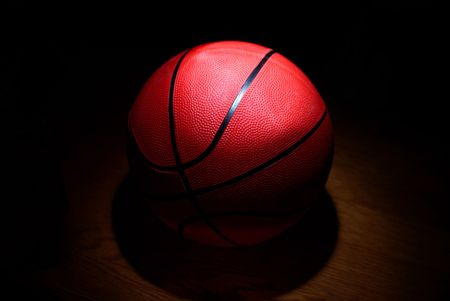 A basketball in the spotlight on a wood floor Stock Photo