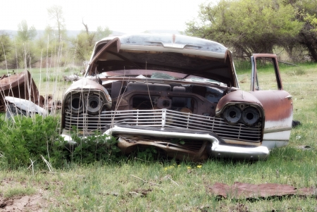 An old abandoned car in the middle of a field photo