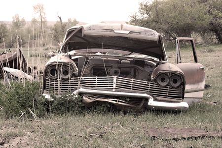 An old abandoned car in the middle of a field