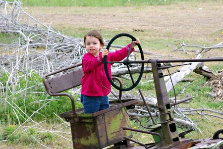 A little girl standing in the seat of an old tractor