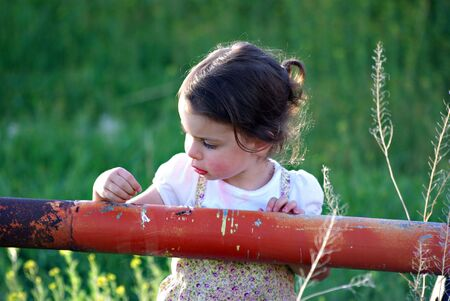 A little girl playing in a field Stock Photo