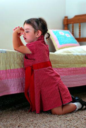 Ein junges Mädchen, die nach unten sagen ein Gebet Knien