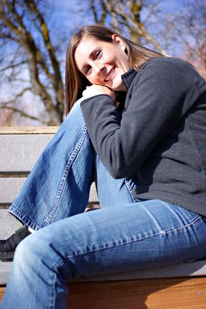 A beautiful young woman sitting on a bench Stock Photo