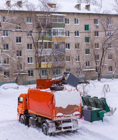 loads: orange garbage truck loads of trash containers in winter Editorial