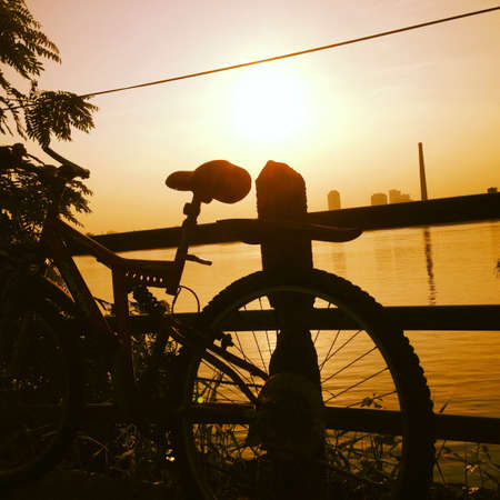 beside: Silhouette of bicycle beside water in Thailand
