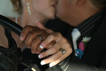 bride and groom kissing with rings in focus