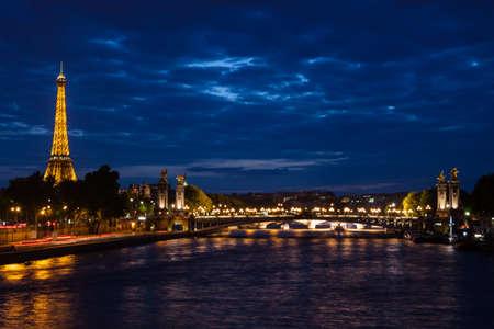 seine: Parijs, Frankrijk, 9 juni 2011: Eiffeltoren en Pont Alexandre III 's nachts. De Eiffeltoren is het meest bezochte monument van Frankrijk met ongeveer 6 miljoen bezoekers per jaar.