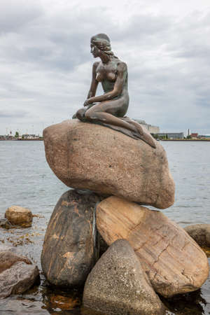 Copenhagen, Denmark - 10 August 2012: The Little Mermaid Statue by Edvard Eriksen, 1913, iconic symbol of Copenhagen sitting on a rock in the harbor looking out to sea at the Langelinie promenade.