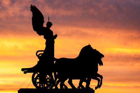 Rome at dusk: silhouette of the goddess Victoria over the National Monument to Vittorio Emanuele II photo