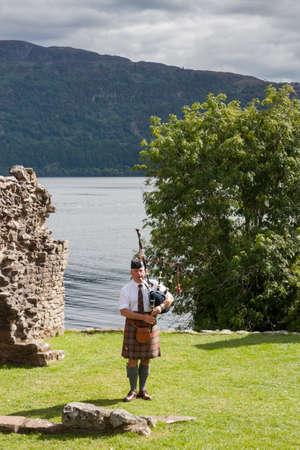 highlander: URQUHART CASTELLO, REGNO UNITO - 13 agosto:. Scottish Highlander indossare kilt e cornamuse a giocare al castello di Urquhart, il 13 Agosto 2013 Castello di Urquhart si siede accanto a Loch Ness nelle Highlands della Scozia.