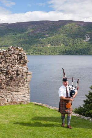 URQUHART CASTLE, UNITED KINGDOM - AUGUST 13: Scottish Highlander wearing kilt and playing Bagpipe at Urquhart Castle, on August 13, 2013. Urquhart Castle sits beside Loch Ness in the Highlands of Scotland.