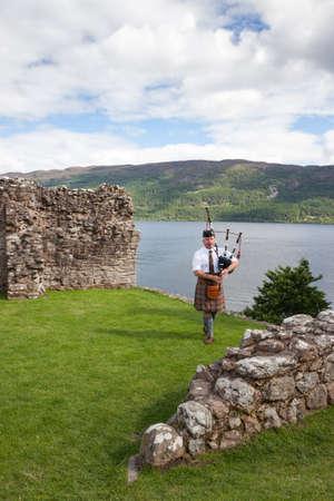 highlander: URQUHART CASTILLO, Reino Unido - 13 de agosto:. Scottish Highlander vistiendo kilt y tocando la gaita en el castillo de Urquhart, en 13 de agosto 2013 el castillo de Urquhart se encuentra al lado del Lago Ness, en las Tierras Altas de Escocia. Editorial