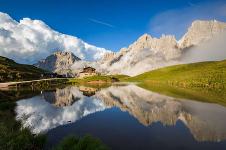 The Pale di San Martino peaks (Italian Dolomites) reflected in the water, with an alpine chalet on background.