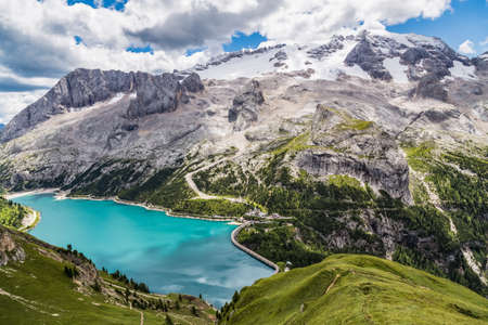 View of the Marmolada, also known as the Queen of the Dolomites and the Fedaia Lake. Marmolada is the highest mountain of the Dolomites, situated in northeast of Italy.